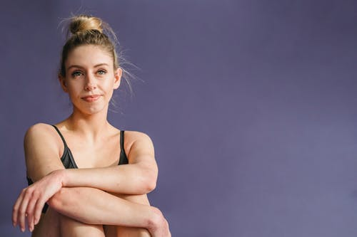 Thoughtful young lady in black underwear sitting in bright studio on purple background