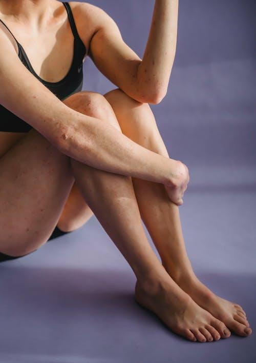 Faceless woman in underwear sitting in studio