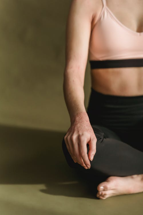 Crop unrecognizable slim female in sportswear with bare shoulders and belly sitting on floor in Padmasana and stretching legs while doing yoga in dark room