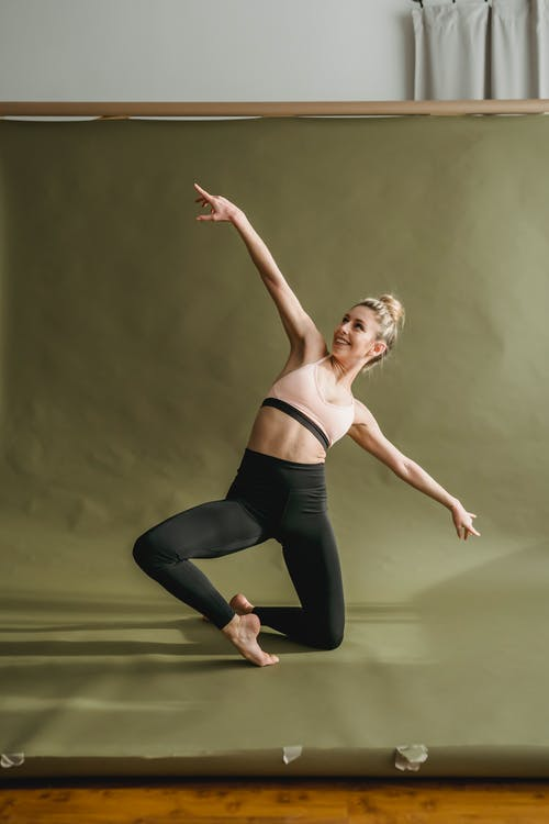 Flexible smiling female in black and pink sportswear looking up and keeping arms apart while standing on knee in dancing pose in studio