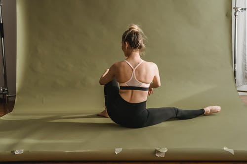 Back view of slim female in black and pink sportswear sitting with extended leg while doing yoga in studio