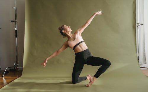 Flexible woman in sportswear doing yoga in light studio