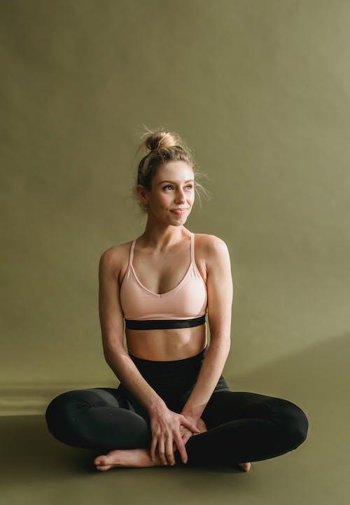 Slim woman in sportswear sitting on floor
