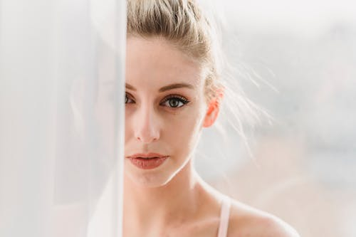 Crop feminine young lady with blond hair standing near window with white curtains and looking at camera in sunlight