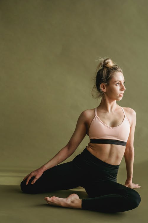 Fit young woman performing Half Pigeon asana while practicing yoga in studio