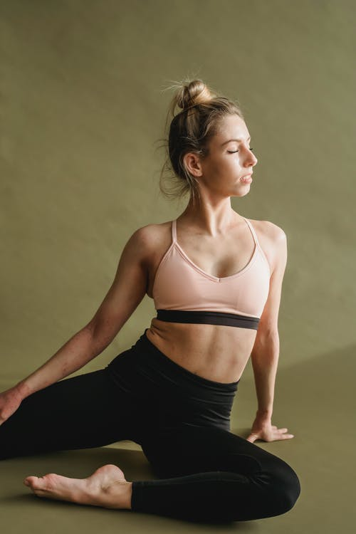 Graceful young woman in activewear stretching body with closed eyes in Half Pigeon pose while practicing yoga in studio
