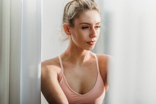 Peaceful young woman looking through window dreamily