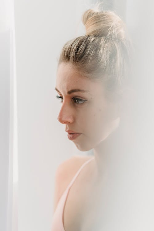 Side view of serious young female with long blond hair in light top standing near white curtain and looking away thoughtfully in daylight at home