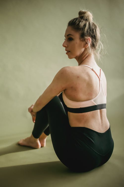 Relaxed young lady sitting on floor after practicing yoga