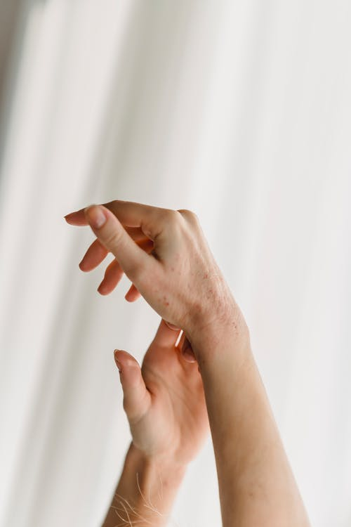 Hands of crop unrecognizable against white curtains