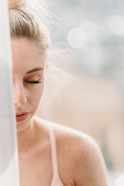 Peaceful woman meditating with closed eyes in sunny morning