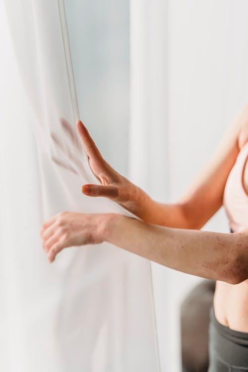 Unrecognizable lady touching soft chiffon curtains in daylight