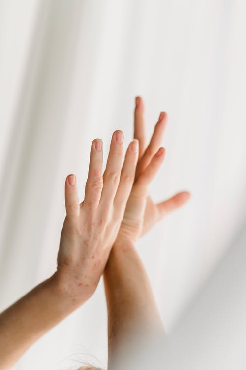 Hands of unrecognizable person with graceful gesture standing with raised arms near window with white curtain in light room at home