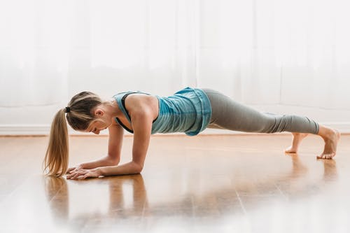 Full body sportive female in activewear doing Forearm plank on floor while training yoga asana in light room at home