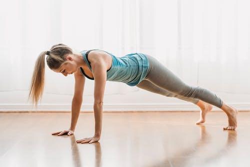 Full body of strong female in sportswear doing Phalakasana asana while practicing yoga in light room on floor at home
