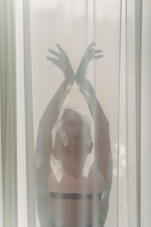 Calm crop female with closed eyes wearing top standing with hands above head behind light curtain in room with sunlight