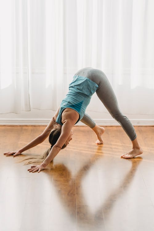 Full body of anonymous slim female in activewear doing Adho Mukha Svanasana on floor at home