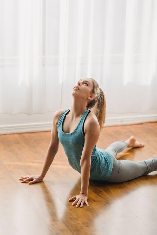 Flexible female in activewear performing Urdhva Mukha Svanasana on timber clean floor at home