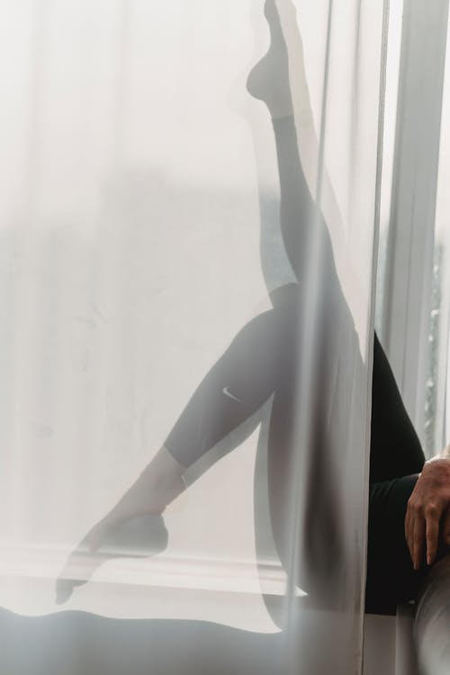 Woman with leg raised on window with curtain