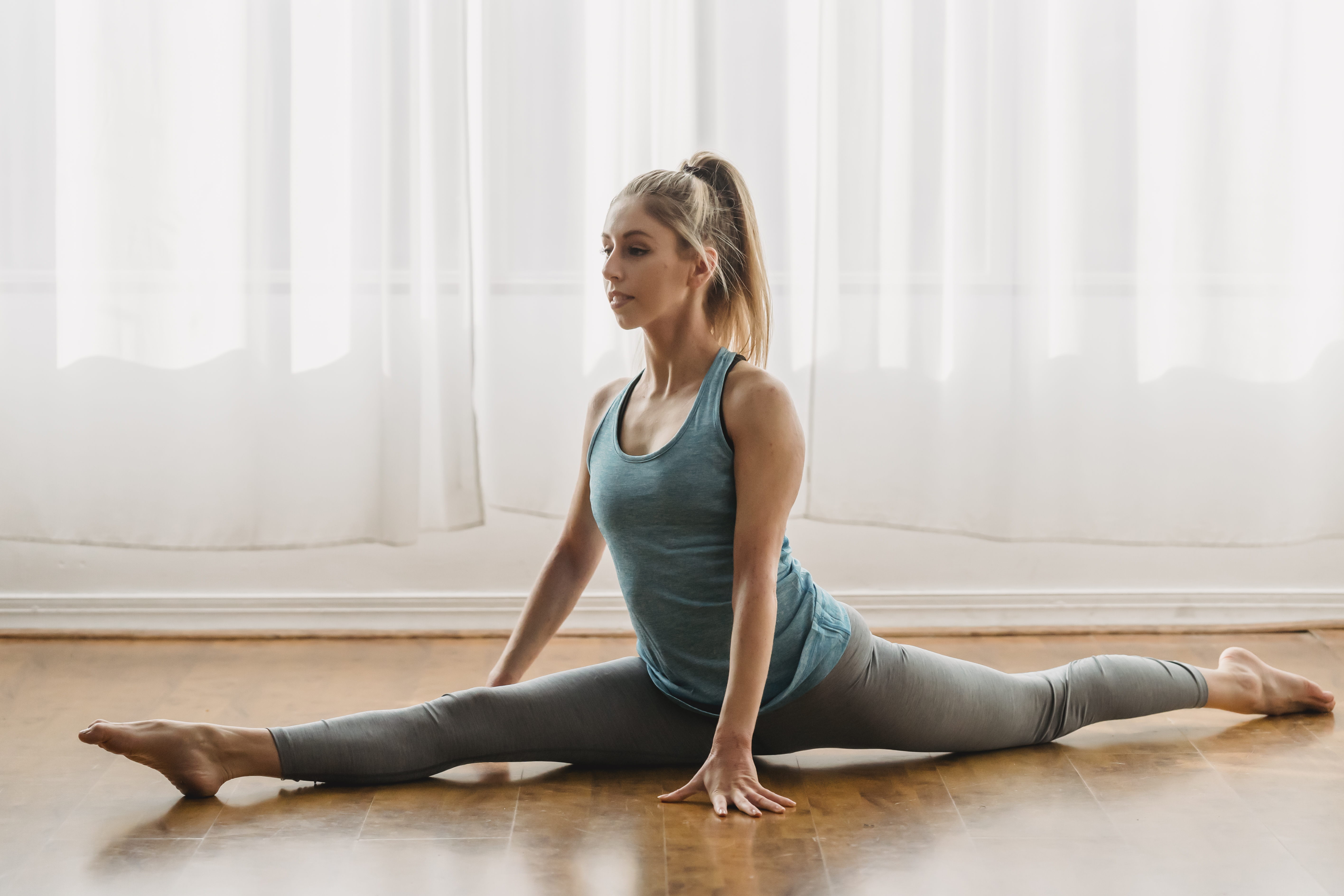 woman stretching on floor near white curtains