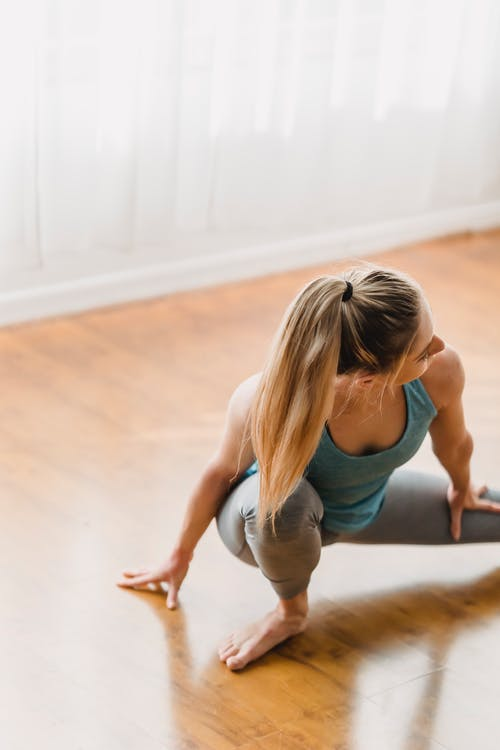 Sporty woman stretching on timber floor