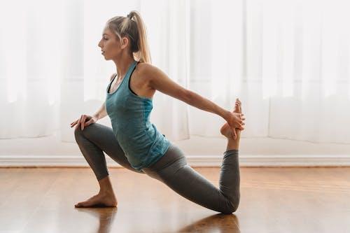 Side view of young flexible female practicing yoga while doing Eka Pada Rajakapotasana at home