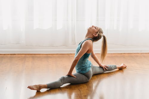 Full body of slim female in sportswear practicing yoga exercises in front split while training in light room on wooden floor