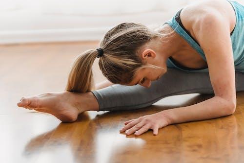 Slim young sportswoman stretching body in split