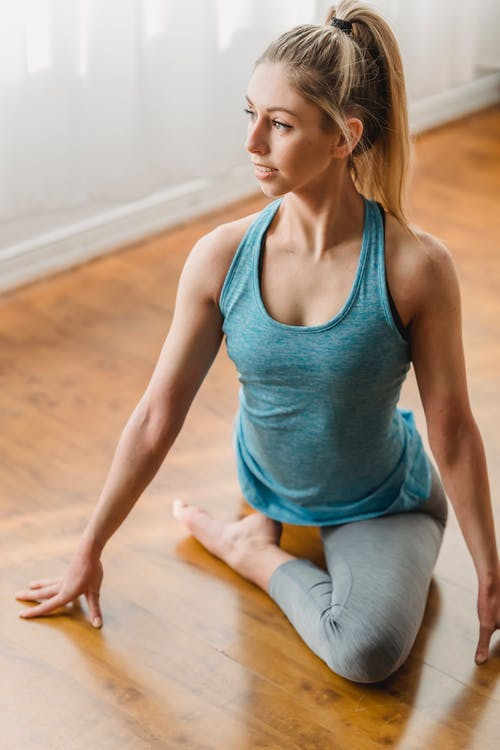 Slim young female athlete in activewear sitting in Half Pigeon position and looking away while doing yoga exercise
