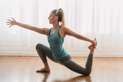 Side view of young slim female in sportswear smiling and looking forward while practicing yoga exercise