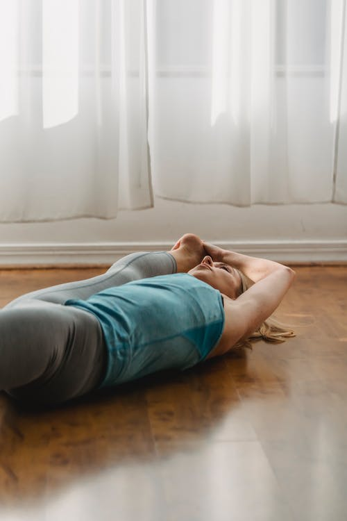 Sportive woman doing Extended supine hand to toe asana