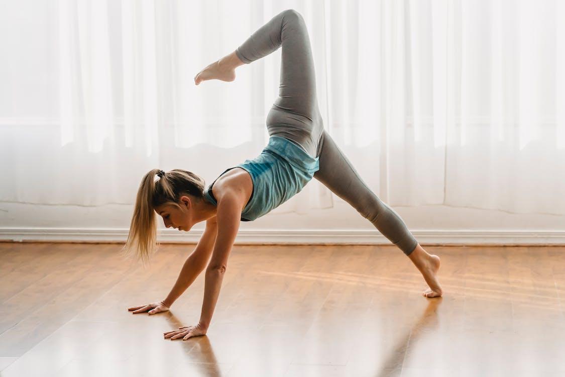 Active woman doing Three legged downward facing dog with hip opener asana