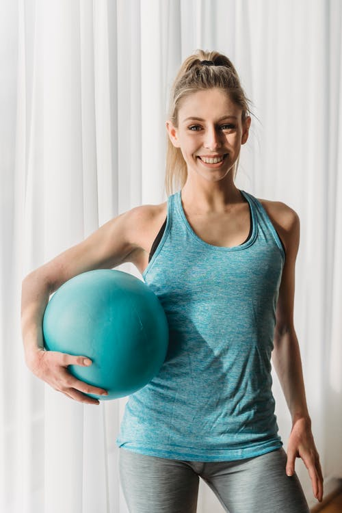 Smiling young lady in activewear holding blue gymnastic ball and looking at camera while standing in light room