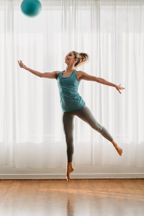 Smiling slim female in sportswear jumping up with fit ball spreading arms and stretching forefeet on sunny day in light room in dance studio