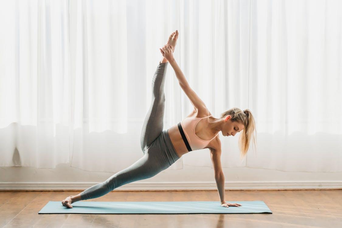 Slim female in sportswear standing in Utthita Vasisthasana pose while practicing yoga in light room at home