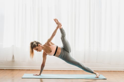 Woman doing yoga in Plank Extended Side pose