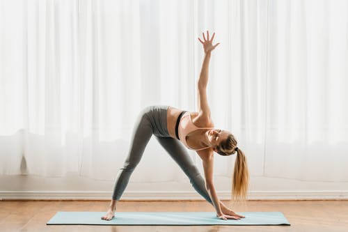 Fit female in sportswear standing in Trikonasana pose while practicing yoga in light room at home