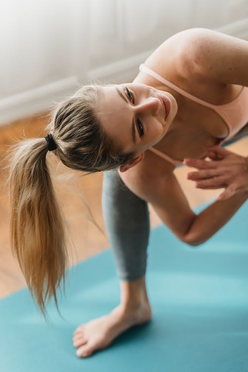 Young slim female in sportswear doing yoga in pose of Revolved Crescent Lunge on Knee with prayer hands while practicing yoga in studio