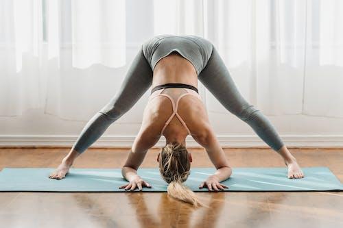 Fit female in sportswear doing yoga in Prasarita Padottanasana pose with bent back on mat in light room