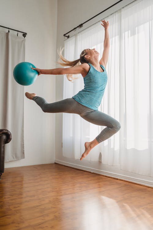 Sporty young woman jumping with medicine ball during workout