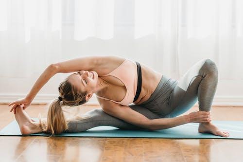 Fit young woman doing Parivrtta Janu Sirsasana yoga pose in studio