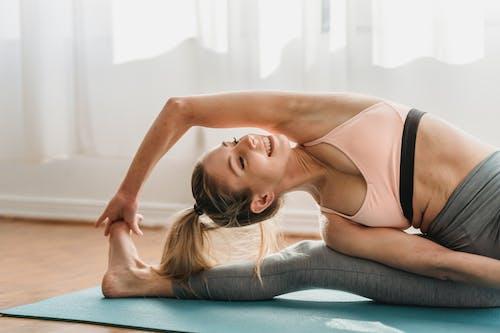 Smiling young flexible female yogi with blond hair in activewear performing Parivrtta Janu Sirsasana pose during morning practice in light studio