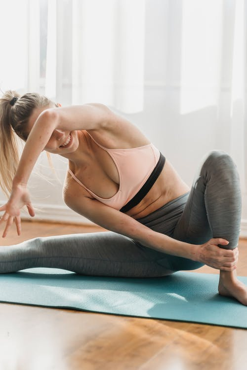 Fit woman stretching body while doing Side Lunge asana on mat