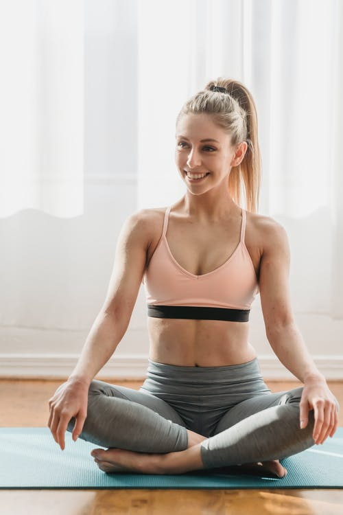 Positive young slim female with long blond hair in sportswear smiling and looking away while recreating in Ardha Padmasana pose during yoga session in light studio