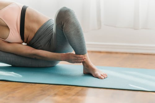Anonymous barefooted lady stretching body during yoga session