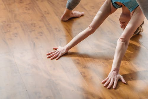 From above of concentrated young barefooted lady in activewear lengthening body while performing Wide Legged Forward Bend I asana during yoga session at home