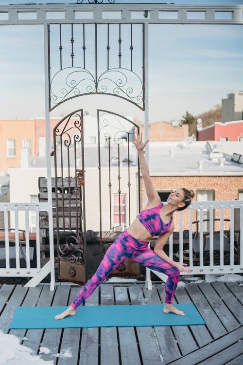 Fit woman practicing yoga on terrace and performing Side Angle asana
