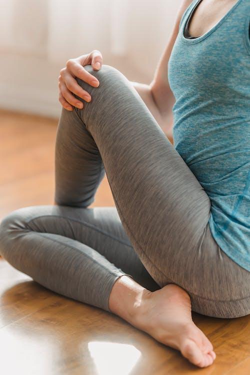 Woman in leggings warming up on floor