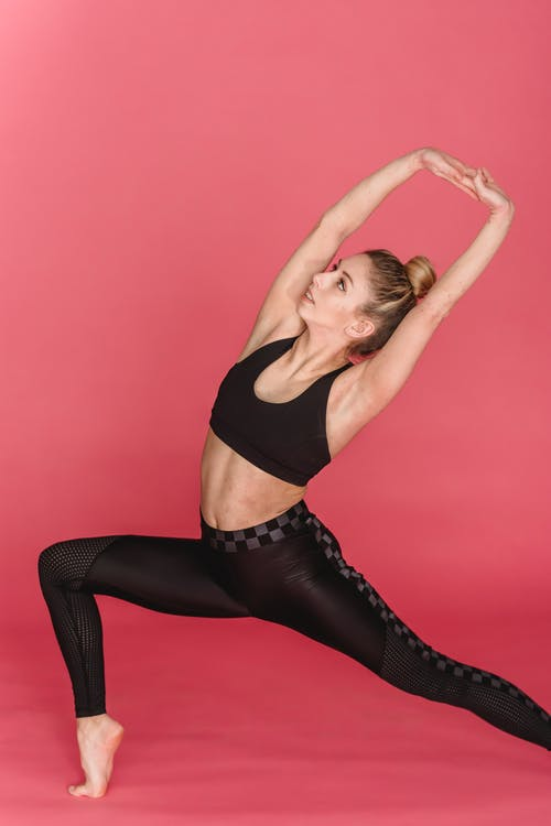 Energetic fit barefoot female in activewear stretching and training on pink background of studio