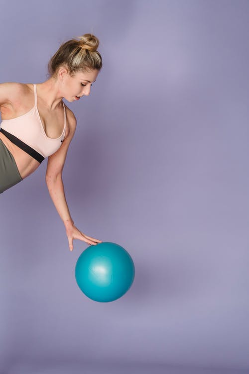 Woman exercising with fitness ball in studio